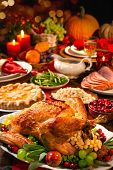 Thanksgiving dinner. Roasted turkey garnished with cranberries on a rustic style table decoraded wit poster