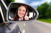 stock photo of four-wheel drive  - woman driving a car on a road with thumbs up in the mirror - JPG