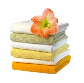 stack of colorful towels with  amaryllis flower isolated on white