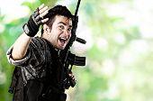 Постер, плакат: Портрет молодой солдат работает на фоне диких джунглей