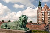White Clouds Over Lion Bronze Sculpture Guard At The Entrance Of Rosenborg Castle, Built In 17th Cen poster