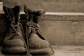 stock photo of work boots  - Old ratty pair of work boots on the steps - JPG