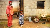 foto of cinder block  - Black African little girl and her mother in traditional clothing at home - JPG