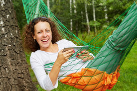 image of birchwood  - Young smiling woman lies in hammock with tablet PC outdoors at birchwood - JPG