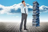 Thoughtful businessman with hand on chin against stack of books against sky