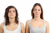 pic of envy  - Two girls looking each other angry isolated on a white background - JPG