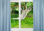 Window With Curtains Overlooking The Garden With A Hammock