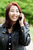 picture of mongolian  - Mongolian girl talking on a phone outside - JPG