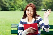 stock photo of mongolian  - Mongolian girl with a book in the park - JPG