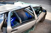 stock photo of blown-up  - Close up side view of a silver motor car crumpled and destroyed in an accident with its windows blown out and shattered and roof caved in - JPG