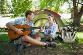 stock photo of serenade  - Cute man serenading his girlfriend on camping trip on a sunny day - JPG