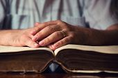stock photo of bible verses  - Male hands on 150 year old open Bible  - JPG