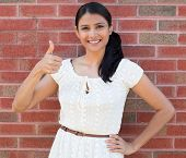 foto of terrific  - Closeup portrait young pretty smiling woman student customer giving thumbs up sign isolated red brick background - JPG