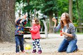 pic of playground  - Happy mother and two little children playing together with soap bubbles on playground in summer - JPG