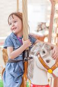 foto of amusement park rides  - Young girl riding carousel horse at amusement park - JPG