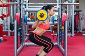 image of squatting  - Woman in gym sport exercising squating with barbell lifting weights - JPG