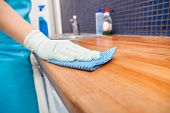foto of kneeling  - Closeup Of Young Woman Wearing Apron Cleaning Kitchen Worktop - JPG