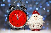 pic of father time  - Santa Claus or Father Frost and vintage alarm clock with red dial on christmas lights background - JPG