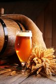 picture of keg  - Beer barrel with beer glass on table on wooden background - JPG