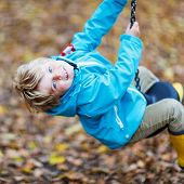 picture of kiddie  - Little toddler child in blue rain jacket and gumboots having fun with playing chain swing on playground on warm autumn day outdoors