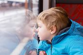 foto of passenger train  - cute child looking out train window outside while it moving - JPG