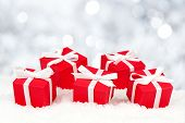 picture of twinkle  - Red gift boxes with white ribbon in snow over a twinkling silver background - JPG