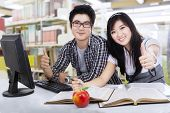 foto of indian apple  - Happy student couple showing thumbs - JPG