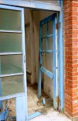 stock photo of framing a building  - The broken door frame of a dilapidated and deserted building - JPG