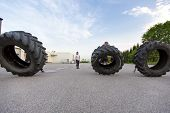 stock photo of heavy  - Fitness group or team flipping heavy tires outdoor - JPG