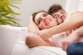 picture of aroused  - love understanding are what this couple shows off while lying on their living room sofa embracing and enjoying