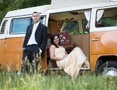 picture of campervan  - Happy just married couple in an orange classic camper van parked outside in a green field ready for camping and a piknick - JPG
