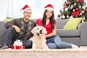 foto of dog christmas  - Young couple celebrating Christmas with their dog at home - JPG