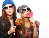 image of swag  -  portrait of two young pretty hipster girls wearing  hats and sunglasses holding candys - JPG