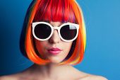picture of wig  - beautiful woman wearing colorful wig and white sunglasses against blue background - JPG