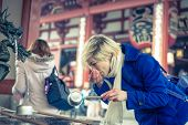 stock photo of woman dragon  - woman drinking water in sensoji temple for purification ritual - JPG