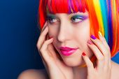 image of wig  - beautiful woman wearing colorful wig and showing colorful nails against blue background - JPG