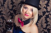 stock photo of cabaret  - beautiful cabaret woman holding a glass of red wine against retro wallpapers - JPG