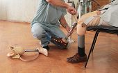 stock photo of amputee  - Hands machinery governing prosthetic leg on man - JPG