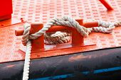 pic of bollard  - Red steel bollard with ropes mounted on a ship deck - JPG