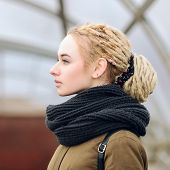 stock photo of dreadlocks  - Closeup portrait of young beautiful blonde woman in olive parka with a dreadlocks bun hairstyle - JPG