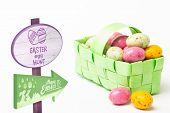 picture of easter basket  - Easter egg hunt sign against colourful easter eggs in a green wicker basket - JPG