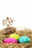 stock photo of laying eggs  - Easter egg hunt sign against three foil wrapped easter eggs nestled in straw nest - JPG