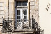 picture of neglect  - Grunge weathered old crumbling balcony with wooden door of neglected townhouse - JPG
