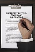picture of fill  - Man filling agreement between owner and contractor document - JPG