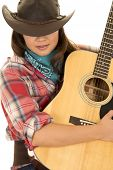picture of cowgirls  - A cowgirl with her eyes hidden holding on to her guitar - JPG