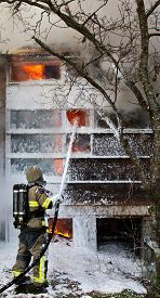 pic of firemen  - Fireman using foam to put out fire in house real world fire - JPG
