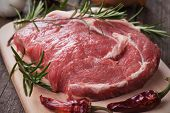 picture of ribeye steak  - Raw ribeye steak on wooden board with chili peppers and rosemary - JPG
