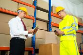 image of warehouse  - Warehouse Worker Checking The Inventory With Manager In A Large Warehouse - JPG