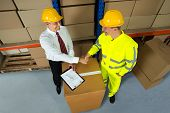 picture of warehouse  - Smiling Warehouse Manager And Worker Shaking Hands In Warehouse - JPG