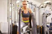 picture of battle  - Young woman working out with battle ropes at a gym - JPG